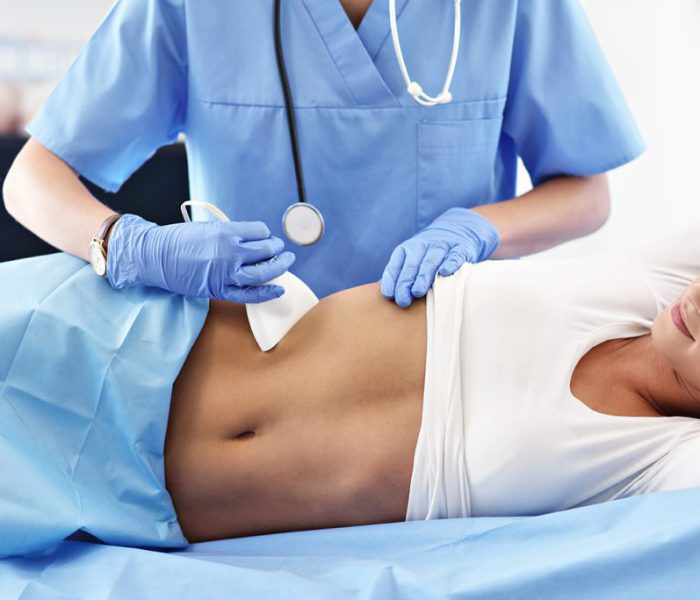 Adult woman having abdomen ultrasound tests at female doctor's office